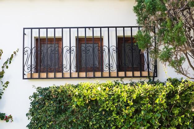 デザイン、建築、エクステリアのコンセプト-白いファサードに格子のある3つの窓。