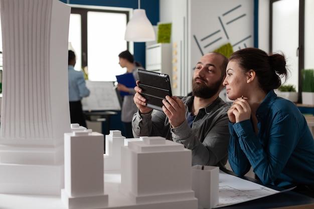 オフィスに座っている設計アーキテクチャの同僚