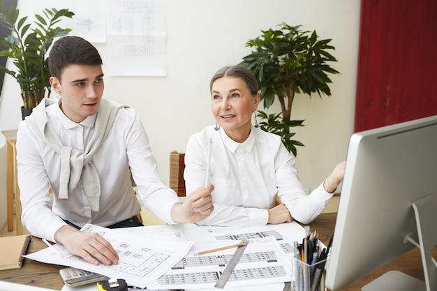 Design, architecture and teamwork concept. beautiful mature female engineer having inspired look while discussing new residential housing project with her creative skillful young man coworker