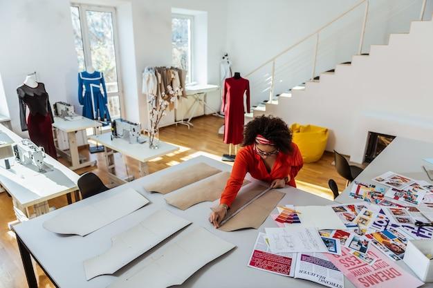 Дизайнерские ткани. концентрированный фигурный афроамериканский дизайнер с рулеткой для вырезания макета из бумаги
