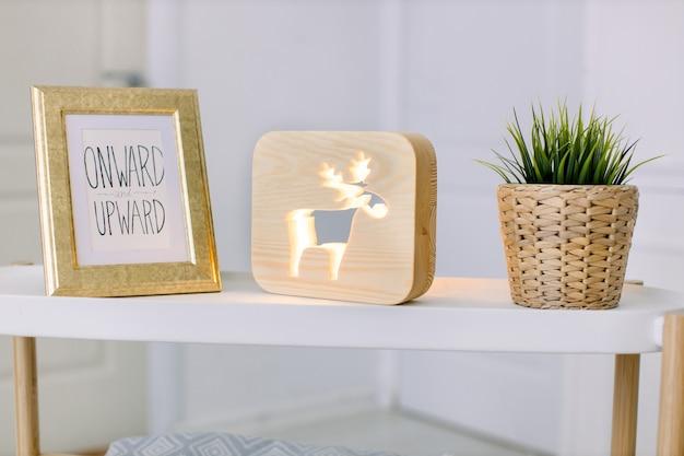 현대 가정 장식의 디자인 구성. 빈티지 액자, 사슴 그림이있는 장식용 나무 램프, 고리 버들 화분의 인공 식물이있는 밝은 거실의 세련된 테이블.