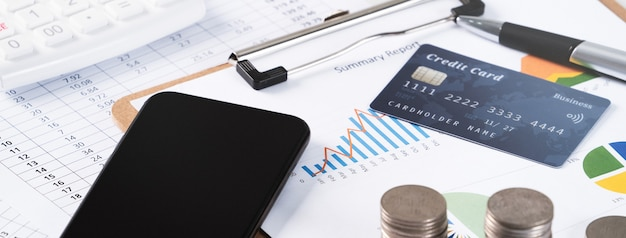 Design concept of annual summary analysis review report with calculator, paying with electronic device and credit card.