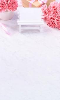디자인 개념-대리석 흰색 배경, 평면도, 복사 공간에 카네이션의 아름 다운 무리를 닫습니다. 어머니의 날 선물 아이디어 영감.