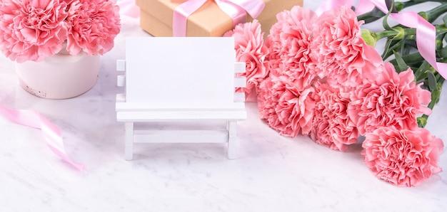 디자인 개념-대리석 흰색 배경, 평면도, 복사 공간에 카네이션의 아름 다운 무리를 닫습니다.