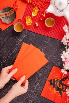 Design concept of chinese lunar january new year - woman holding, giving red envelopes (ang pow, hong bao) for lucky money, top view, flat lay, overhead above. the word 'chun' means coming spring.