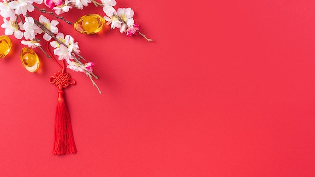Design concept of chinese lunar new year - beautiful chinese knot with plum blossom isolated on red background, flat lay, top view, overhead layout.