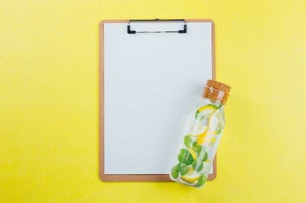 Design concept of mockup clip board and lemon mint water on yellow background.