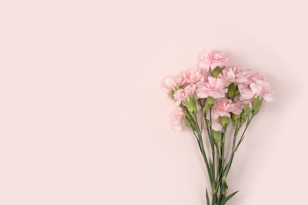 Design concept of mother's day holiday greeting design with carnation bouquet on pastel pink table background