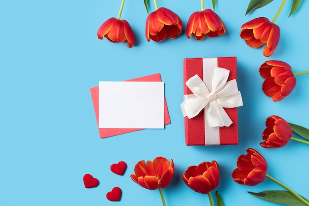 Design concept of mother's day holiday greeting gift with red tulip bouquet and card on bright blue table background
