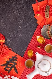 Концепция дизайна китайского лунного января нового года - праздничные аксессуары, красные конверты (ang pow, hong bao), вид сверху, плоская планировка, над головой выше. слово «чун» означает наступающая весна.