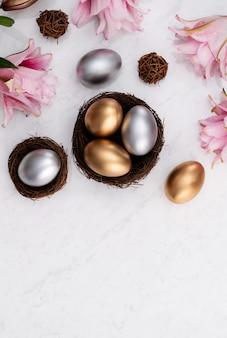 밝은 대리석 흰색 테이블 배경에 분홍색 백합 꽃과 둥지에 황금과 부활절 달걀의 디자인 개념.