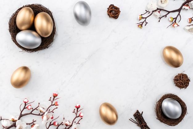 밝은 대리석 흰색 테이블 배경에 흰색 매화 꽃과 둥지에 황금과 부활절 달걀의 디자인 개념.
