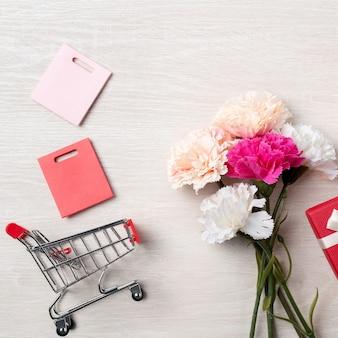 카네이션 꽃, 크리스마스 선물 아이디어와 나무 배경에 장바구니와 어머니의 날 인사말의 디자인 개념.