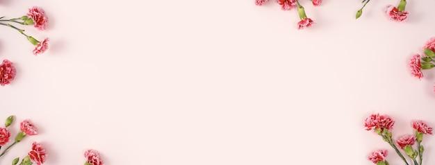 파스텔 핑크 테이블 배경에 카네이션 꽃다발과 어머니의 날 휴일 인사말 디자인의 디자인 컨셉