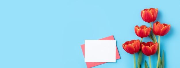 밝은 파란색 테이블 배경에 빨간 튤립 꽃다발과 카드와 어머니의 날 휴일 인사말 선물 디자인의 디자인 컨셉