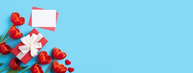 Концепция дизайна праздничного подарка на день матери с букетом красных тюльпанов и картой на ярко-синем фоне стола