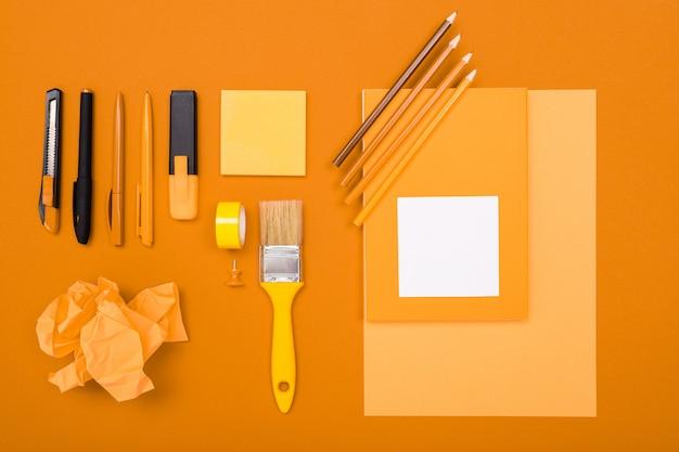 デザインのコンセプト。文房具とオレンジ色の空白の背景に紙でブラシ