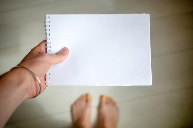 Концепция дизайна - вид сверху руки с серебряным браслетом держит блокнот с copyspace, на заднем плане - деревянный пол и ноги в размытом виде. вид сверху