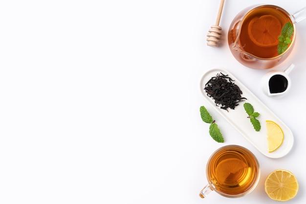 白いテーブルの背景に黄色のレモンとミントの葉と蜂蜜紅茶のデザインコンセプト上面図。
