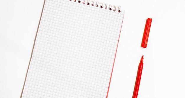 Концепция дизайна - вид сверху красной спиральной тетради и коллекции цветных карандашей, изолированные на белом фоне