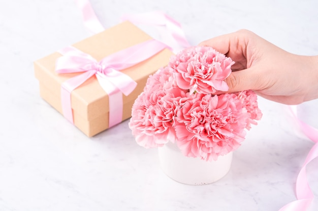 Design concept - woman giving carnations bouquet on marble white background, top view, copy space, close up.