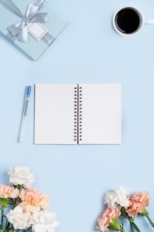 Design concpet of mother's day greeting with carnation flower, holiday gift idea and notebook diary on mother's desk background.