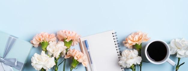 어머니 책상 배경에 카네이션 꽃, 크리스마스 선물 아이디어 및 노트북 일기와 함께 어머니의 날 인사말 Concpet 디자인. 프리미엄 사진
