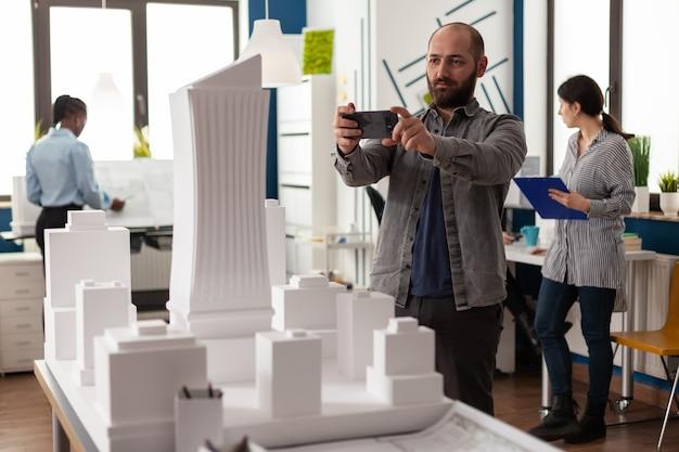 建築構造のプロジェクトのためにスマートフォンを見ている設計コンストラクター。現代開発のための建物モデルマケット都市計画レイアウトを検査する机に立っているエンジニア