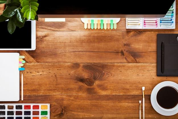 創造的な作業テーブルのコンセプト、茶色の木製の机の上のコンピューターの塗料をデザインします。