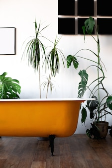 Design of loft interior of bathroom or room. white walls with free copyspace. trend green - palm leaves on background. modern design yellow bath.