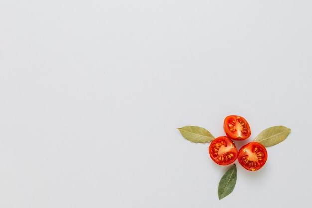 Design made with aromatic bay leaves and halved cherry tomatoes on the corner of white background