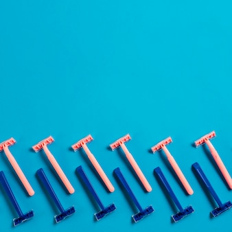 Design made with row of blue and pink razors on blue background