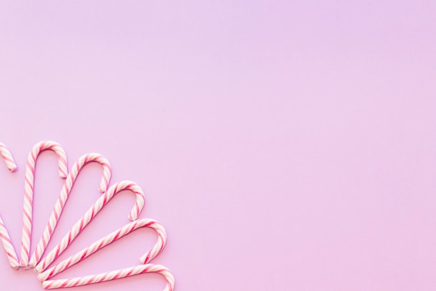Design made with xmas candy cane on the pink background corner
