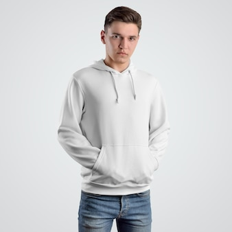 若い男の白いパーカーのモックアップのデザイン。店舗でのプレゼンテーション用の服、正面図のテンプレート。