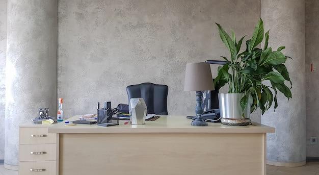 Дизайн рабочего места в офисе с современным оборудованием и удобствами на сером стенном фоне.