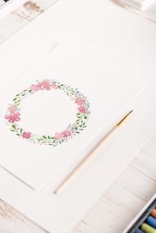 紙に水彩で描かれた花のフレームのデザイン
