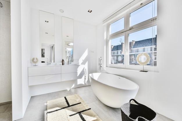 広々とした太陽に照らされたバスルームのデザイン。二重の洗面台と鏡、窓の近くに大きな白いバスタブがあります。