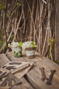 Design of the photo zone in a rustic style, old wooden doors and boards with tools and spring flowers.