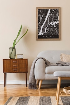 Design scandinavian home interior of living room with  map, stylish wooden commode, sofa, flowers in vase and elegant personal accessories. modern home staging. beige concept.