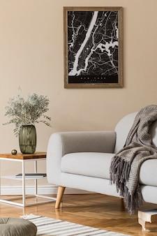 지도, 세련된 커피 테이블, 회색 소파, 격자 무늬, 꽃병에 베개 꽃 및 우아한 개인 액세서리가있는 거실의 스칸디나비아 가정 인테리어를 디자인하십시오. 현대적인 홈 스테이징.