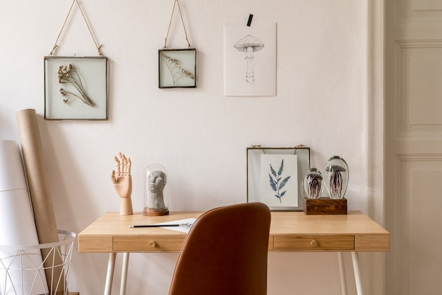 Design scandinavian interior of home office space with a lot of photo frames, wooden desk, brown chair, plants, office and personal accessories. stylish neutral home staging..