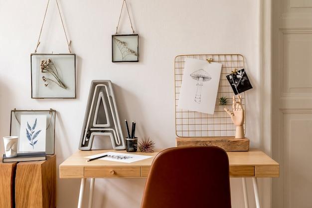 모의 사진 프레임, 나무 책상, 갈색 의자, 네온 편지, 사무실 및 개인 액세서리가 많은 홈 오피스 공간의 스칸디나비아 인테리어를 디자인하십시오. 세련된 중립적 인 홈 스테이징. 주형.