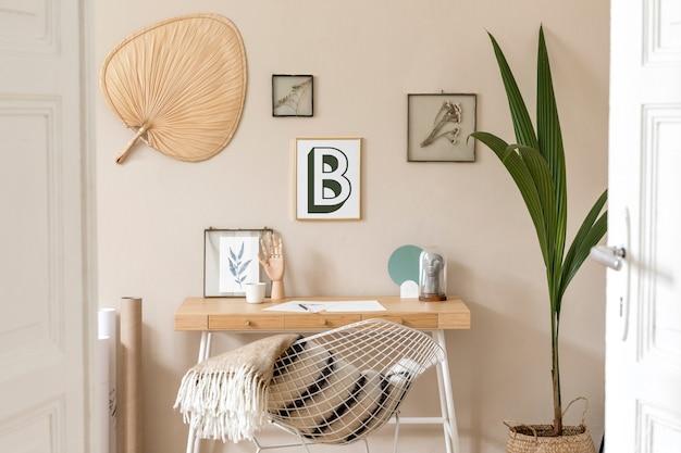 많은 모의 사진 프레임, 나무 책상, 흰색 안락의자, 식물, 사무실 및 개인 액세서리가 있는 홈 오피스 공간의 스칸디나비아 인테리어를 디자인합니다. 스타일리시한 뉴트럴 홈 스테이징. 주형.