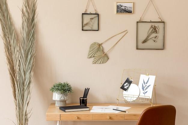 많은 사진 프레임, 나무 책상, 갈색 의자, 식물, 사무실 및 개인 액세서리로 홈 오피스 공간의 스칸디나비아 인테리어를 디자인하십시오. 세련된 중립적 인 홈 스테이징 ..