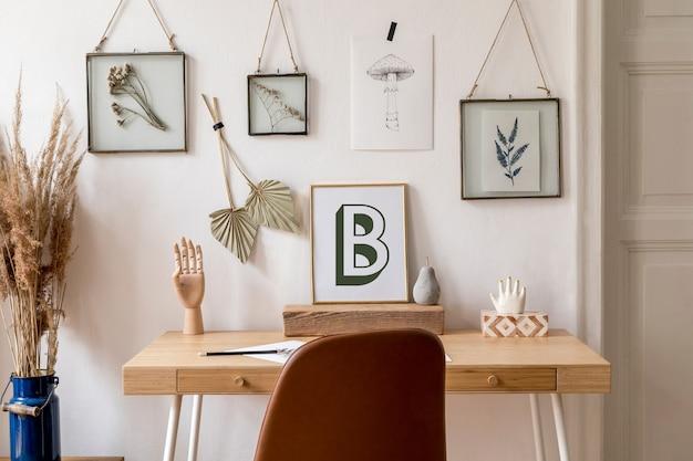 모의 사진 프레임, 나무 책상, 갈색 의자, 사무용품 및 개인 액세서리로 홈 오피스 공간의 스칸디나비아 인테리어를 디자인합니다. 스타일리시한 뉴트럴 홈 스테이징. 주형.