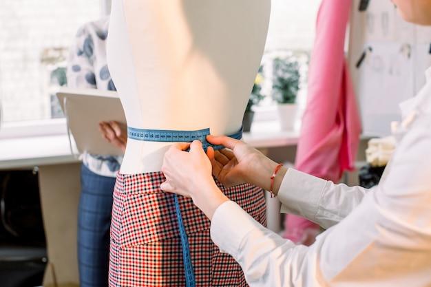 Студия дизайна. брюки на манекен и измерительная лента в руках женщины. портниха берет манекен, измеряет манекен с рулеткой в мастерской, студии дизайна одежды