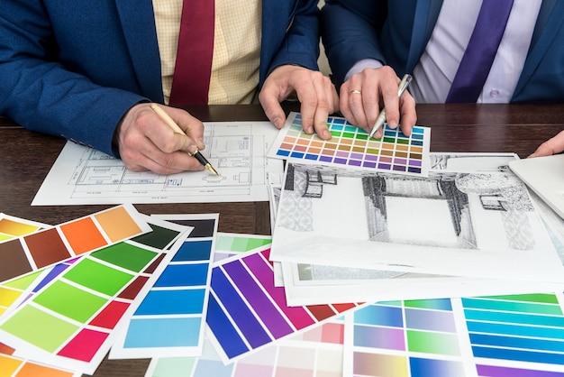 Команда дизайнеров работает в офисе над домашним проектом. эскиз квартиры в цветовой палитре. современный милый дом.