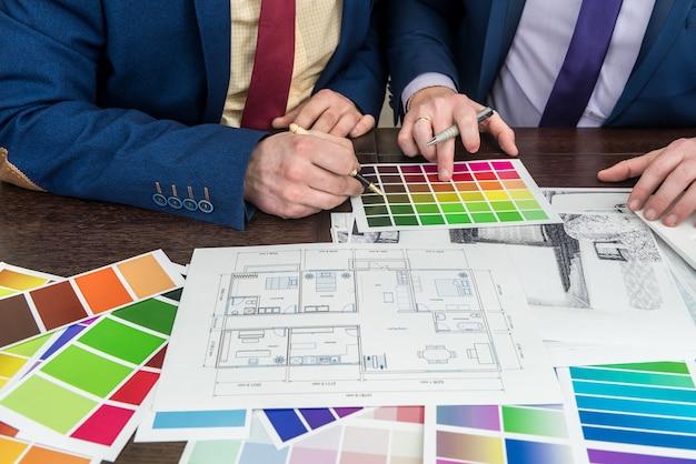 家のプロジェクトの下でオフィスで働くデザインチーム。カラーパレットでアパートのスケッチ。モダンなスイートホーム。
