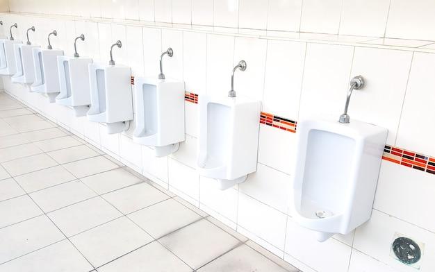 Design of white ceramic urinals for men in public toilet room