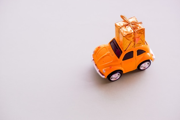 パステルの壁に分離された屋根の上のギフトボックスを提供する黄色のビンテージレトロなおもちゃの車をデザインします。クリスマス、正月、誕生日、プレゼント。配送、ショッピング、販売コンセプト。